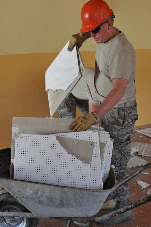 Wyoming Air National Guard's Tech. Sgt. Paul Schultz, 153rd Civil Engineer Squadron, pushes a wheelbarrow of ceiling tile out of the NATO School recreation center site Aug. 17, 2012 in Oberammergau, Germany. Airmen from the 153rd CES are putting their skills to work as they conduct their annual training. (U.S. Air Force photo by Staff Sgt. Natalie Stanley)