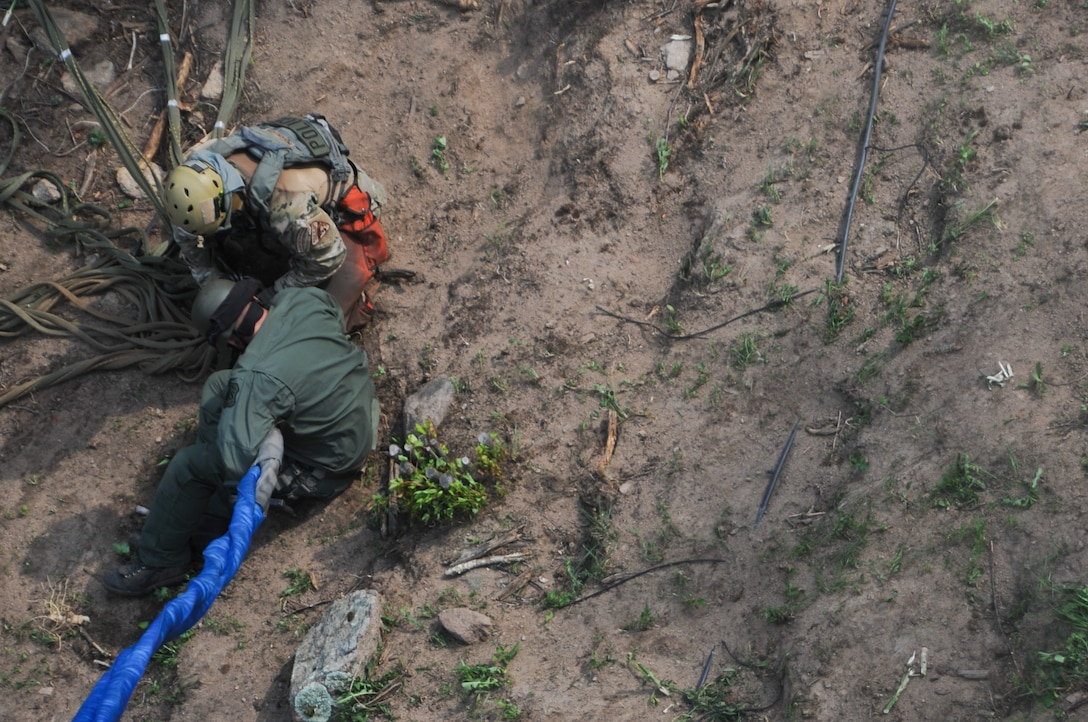 After clearing the area of marijuana plants, counterdrug personnel load the plants into a net and secure the net to a helicopter hoist for extraction from a remote hillside near Rye, Colo., Aug. 15, 2012. Using a UH-60 helicopter, Colorado National Guardsmen helped move an estimated 7,000 to 9,000 marijuana plants -- nearly $15 million street value -- from two remote grow sites located on private property. Members of the Colorado National Guard Joint Counter-Drug Task Force's Drug Interdiction section were called to assist the Pueblo County Sheriff's Office move the plants, which are growing in steep terrain that's impassible by motor vehicle. The operation is largest marijuana bust in Pueblo County history and one of the largest ever in Colorado. (Official Air National Guard photo by Master Sgt. Cheresa D. Theiral)