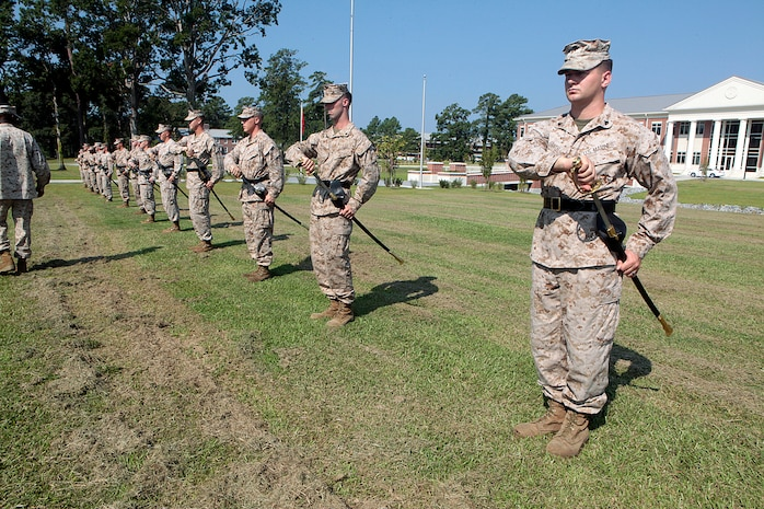 "Cherry Point Corporals Leadership Class 274-12 hold a ""draw sword"" during an introduction to sword manual, Aug. 17. The three-week course is the first Professional Military Education class enlisted Marines attend and focuses on leadership, history and tradition of Marine Corps corporals."