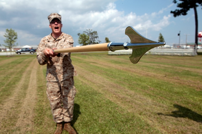 "Cpl. Nathan W. Poulter, an EA-6B Prowler airframe mechanic and student with class 274-12, ""presents guidon"" while shouting the command during an introduction to guidon manual, Aug. 17. The three-week course is the first Professional Military Education class enlisted Marines attend and focuses on leadership, history and tradition of Marine Corps corporals."