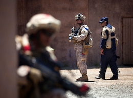 Sgt. Daniel McCaughern (left), a squad leader with 1st Platoon, India Company, 3rd Battalion, 3rd Marine Regiment, and 24-year-old native of Deer Park, N.Y., looks back on his Marines during a non-lethal weapons training scenario in a simulated urban village on Marine Corps Training Area Bellows, Hawaii, Aug. 15, 2012. The training was part of a two-week test readiness review fielded by the Quantico, Va.-based Joint Non-Lethal Weapons Directorate and the Marine Corps Forces, Pacific Experimentation Center. The DoD Non-Lethal Weapons Program, headed by Commandant of the Marine Corps Gen. James Amos, trains operating forces on escalation of force options to minimize casualties and collateral damage, said Kelley Hughes, a directorate spokesperson.