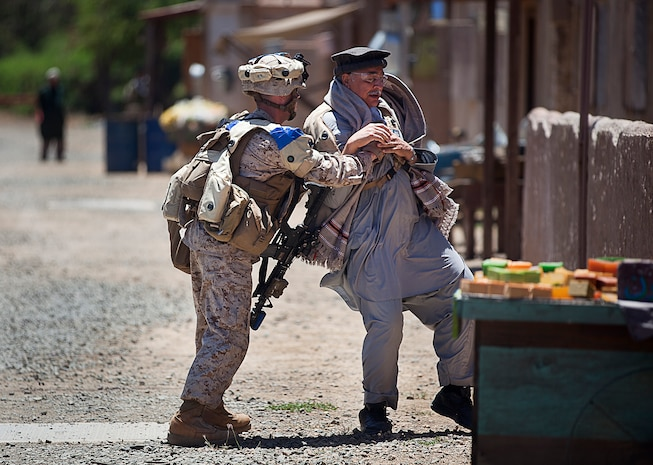 Sgt. Daniel McCaughern (left), a squad leader with 1st Platoon, India Company, 3rd Battalion, 3rd Marine Regiment, and 24-year-old native of Deer Park, N.Y., detains a non-compliant role-player during non-lethal weapons training in a simulated urban village on Marine Corps Training Area Bellows, Hawaii, Aug. 15, 2012. The training was part of a two-week test readiness review fielded by the Quantico, Va.-based Joint Non-Lethal Weapons Directorate and the Marine Corps Forces, Pacific Experimentation Center. The DoD Non-Lethal Weapons Program, headed by Commandant of the Marine Corps Gen. James Amos, trains operating forces on escalation of force options to minimize casualties and collateral damage, said Kelley Hughes, a directorate spokesperson.