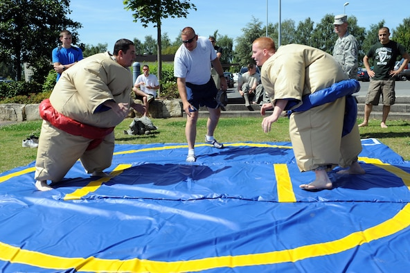 SPANGDAHLEM AIR BASE, Germany – Airman 1st Class Corey Kingsbury, American Forces Network Detachment Nine, and Senior Airman Kodie Hinz, 606th Air Control Squadron, prepare to face off during a sumo wrestling match during an unaccompanied Airmen block party at the wing pavilion here Aug. 17. The event included a drunk goggles obstacle course, sumo wrestling, Polynesian dancers, a dunk tank and a comedy performance. The first sergeants council and the Spangdahlem chiefs group hosted the event. (U.S. Air Force photo by Senior Airman Christopher Toon/Released)