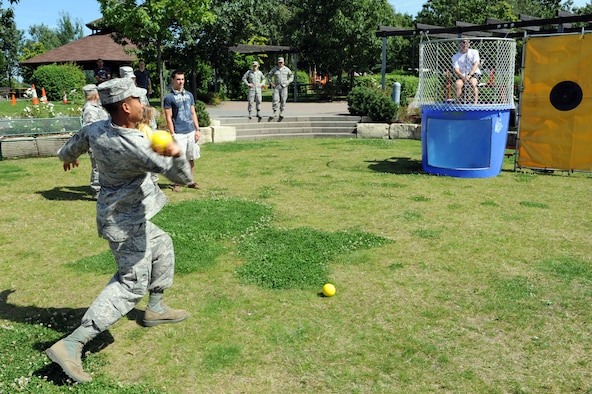 SPANGDAHLEM AIR BASE, Germany – Senior Airman Christopher Lyn, 606th Air Control Squadron, attempts to dunk Chief Master Sgt. Matthew Grengs, 52nd Fighter Wing command chief, during an unaccompanied Airmen block party at the wing pavilion here Aug. 17. The event included a drunk goggles obstacle course, sumo wrestling, Polynesian dancers, dunk tank and a comedy performance. The first sergeants council and the Spangdahlem chiefs group hosted the event. (U.S. Air Force photo by Senior Airman Christopher Toon/Released)