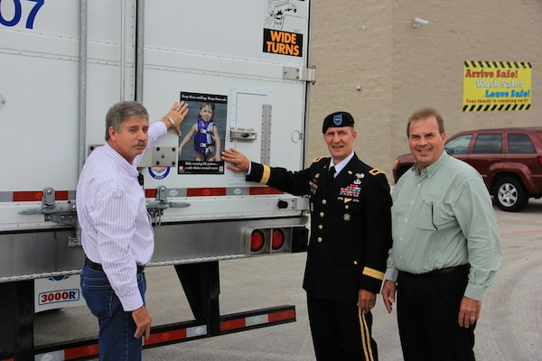DALLAS, Texas — Brig. Gen. Thomas W. Kula, U.S. Army Corps of Engineers Southwestern Division commander (center), joins with Mr. Jim Franck, president of National Carriers, Inc. (right), and Johnny Branstine, maintenance director, to place a water safety sign on one of the 900 tractor trailer trucks owned by the company, Aug. 15, 2012.