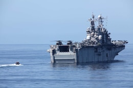 A rigid-hull inflatable boat approaches the USS Peleliu, transporting servicemembers from the USS Rushmore, Aug. 18, during the 15th Marine Expeditionary Unit and Peleliu Amphibious Ready Group's final pre-deployment training evolution, Certification Exercise. The MEU's mission capabilities and performance will be evaluated during the exercise to ensure it is ready to deploy later this year.