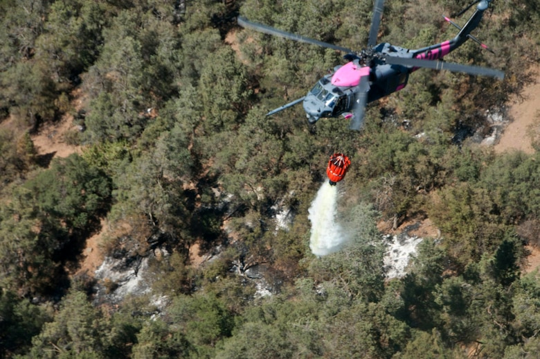 California Air National Guard HH-60G Pave Hawk rescue helicopter and air crew, assigned to the 129th Rescue Wing, releases 500 gallons of water on the Jawbone Complex Fire in Kern County, Calif., Aug. 15, 2012. During the support of the Bureau of Land Management, Kern County fire, and Cal Fire; the 129th Rescue Wing has performed more than 120 bucket drops. (Air National Guard photo by Master Sgt. Julie Avey/Released)