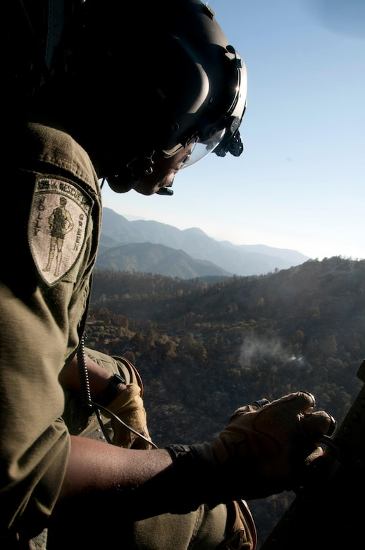 California Air National Guard, Tech. Sgt. Michael Porter, an aerial gunner assigned to the 129th Rescue Squadron, releases water from the bucket attached to an HH-60G Pave Hawk rescue helicopter, while battling the Jawbone Complex Fire in Kern County, Calif., Aug. 15, 2012.. During the support of the Bureau of Land Management, Kern County fire, and Cal Fire; the 129th Rescue Wing has performed more than 120 bucket drops. (Air National Guard photo by Master Sgt. Julie Avey/Released)