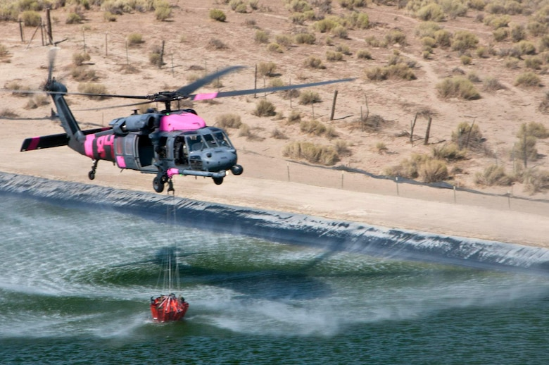 California Air National Guard HH-60G Pave Hawk rescue helicopter and air crew, assigned to the 129th Rescue Wing collect water in preparation for bucket drops over the Jawbone Complex Fire in Kern County, Calif., Aug. 15, 2012. During the support of the Bureau of Land Management, Kern County fire, and Cal Fire; the 129th Rescue Wing has performed more than 120 bucket drops. (Air National Guard photo by Master Sgt. Julie Avey/Released)