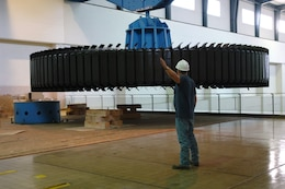 KUTTAWA, Ky. — A crewman with National Electric Coil from Columbus, Ohio guides a 270-ton rotor assembly onto a pedestal at the Barkley Dam Hydropower Plant here, Aug. 16, 2012. The U.S. Army Co