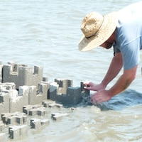 A Charleston District contractor works to construct the oyster castle wall.