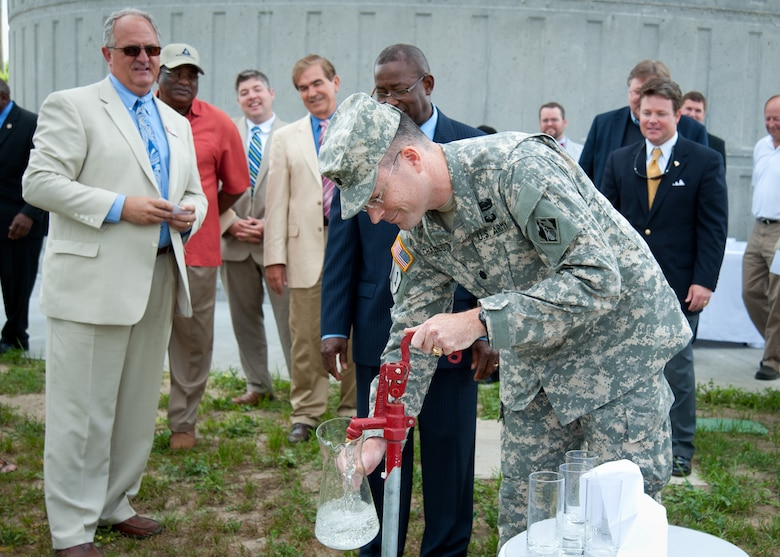 Lt. Col. Ed Chamberlayne pours the first pitcher of water from the new water tower.