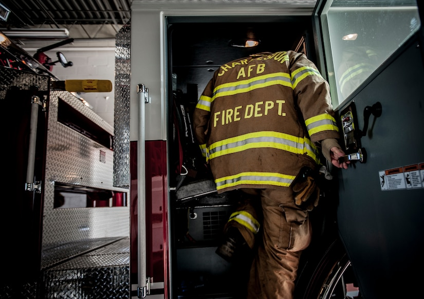 Staff Sgt. Anthony Ankeny, 628th Civil Engineer Squadron firefighter,  climbs into a fire truck during a drill Aug. 9, 2012, at Joint Base Charleston – Air Base, S.C. Each firefighter has six pieces of equipment to put on in less than two minutes when responding to an emergency call. (U.S. Air Force photo/Senior Airman Dennis Sloan)