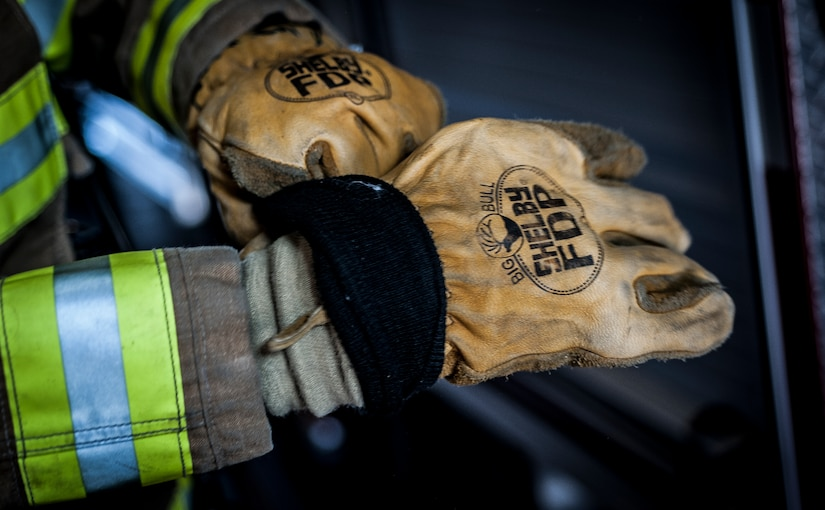 Senior Airman Erik Myles, 628th Civil Engineer Squadron firefighter, puts his gloves on during a drill Aug. 20, 2012, at Joint Base Charleston –Air Base, S.C. Each fire fighter has six pieces of equipment to put on in less than two minutes when responding to an emergency call. (U.S. Air Force photo/Senior Airman Dennis Sloan)