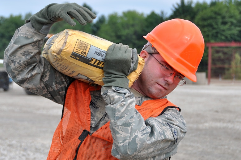 Airman 1st Class Zachary Buhrer, knowledge operations management, 307th Civil Engineer Squadron, transports a bag of cement at Youngstown Air Reserve Station, Vienna, Ohio, Aug. 14, 2012. Buhrer was part of a 29-person detail from Barksdale Air Force Base, La., that spent two weeks at Youngstown assisting the 910 Civil Engineer Squadron build a Prime Base Engineer Emergency Force (Prime BEEF) training area. (U.S. Air Force photo by Master Sgt. Jeff Walston)