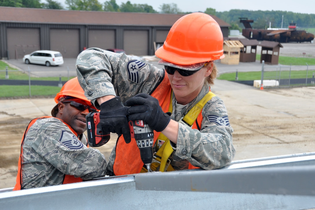 Master Sgt. Alfred Cain, a heating, ventilation, air conditioning and refrigeration technician, holds a support spacer in place as Staff Sgt. Angel Hirschi, a utilities journeyman, secures it to a metal beam at Youngstown Air Reserve Station, Vienna, Ohio, Aug. 14, 2012. Both Airmen were from the 307th Civil Engineer Squadron and were part of a 29-person detail from Barksdale Air Force Base, La., that spent two weeks at Youngstown assisting the 910 Civil Engineer Squadron build a Prime Base Engineer Emergency Force (Prime BEEF) training area. (U.S. Air Force photo by Master Sgt. Jeff Walston)