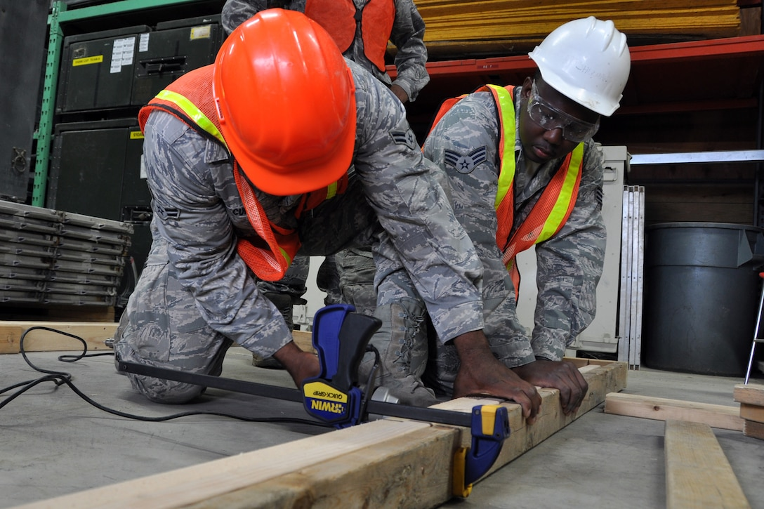 Senior Airman Thorton Allen holds a wood frame as Airman 1st Class Brandon Curry secures it with a screw at Youngstown Air Reserve Station, Vienna, Ohio, Aug. 14, 2012. The frame will be used in the construction of defensive fighting positions (DFP) at a Prime Base Engineer Emergency Force (Prime BEEF) training area. Allen is a heating, ventilation, air conditioning and refrigeration technician, and Curry is an electrician. Both Airmen are assigned to the 307th Civil Engineer Squadron from Barksdale Air Force Base, La. They were part of a 29-person detail from Barksdale that spent two weeks at Youngstown assisting the 910 Civil Engineer Squadron build a training area. (U.S. Air Force photo by Master Sgt. Jeff Walston)