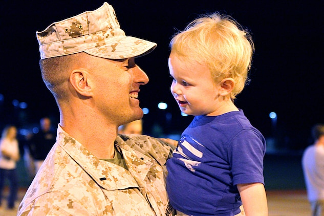 First Lt. Christopher Mcquade, the tactical movement control center officer-in-charge with 1st Marine Division, holds his one-year-old son Landon during a homecoming event here, Aug. 22. Mcquade, a 30-year-old native of Lower Gwynedd Township, Penn., deployed to Afghanistan for seven months in support of Operation Enduring Freedom.