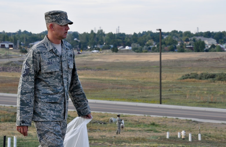 """BUCKLEY AIR FORCE BASE, Colo. – Senior Master Sgt. Shane Enos, 460th Comptroller Squadron and Space Wing Staff superintendent, oversees the clean up behind the wing staff building during a base beautification event Aug. 23, 2012.  """"Base cleanup is essential,"""" he said. """"As Air Force professionals we adhere to the highest standards, and professional appearance is one of them.""""  (U.S. Air Force photo by Staff Sgt. Nicholas Rau)"""