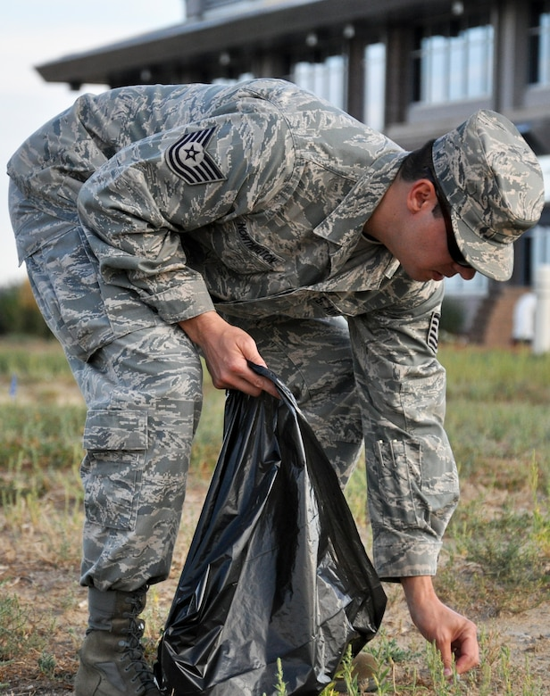 """BUCKLEY AIR FORCE BASE, Colo. – Tech Sgt. Kenneth Northington, 460th Space Wing Safety Office, picks up trash behind the command building during a base beautification event Aug. 23, 2012.  """"Ridding the base of debris, trash (and other hazards) helps prevent possible injury from trips, slips and falls,"""" he said.  """"Also it gives us the opportunity to identify any possible hazardous materials or any safety issues that might not otherwise be identified.""""  (U.S. Air Force photo by Staff Sgt. Nicholas Rau)"""