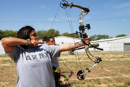 Wounded warrior Spc. Amber Tousha tries out archery for the first time during the Warrior Transition Battalion Adapted Sports Day Aug. 15. (Photo by Maria Gallegos, Brooke Army Medical Center Public Affairs)