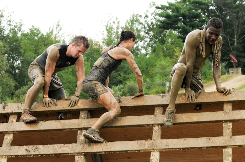 Staff Sgt. Rhon Salmon (right), Massachusetts Air National Guard recruiter, climbs a wall in Amesbury, Mass., Aug. 11, 2012. The wall was the last obstacle of the Spartan Race before the finish line. (Air National Guard photo by Senior Airman Jeremy Bowcock/Released)