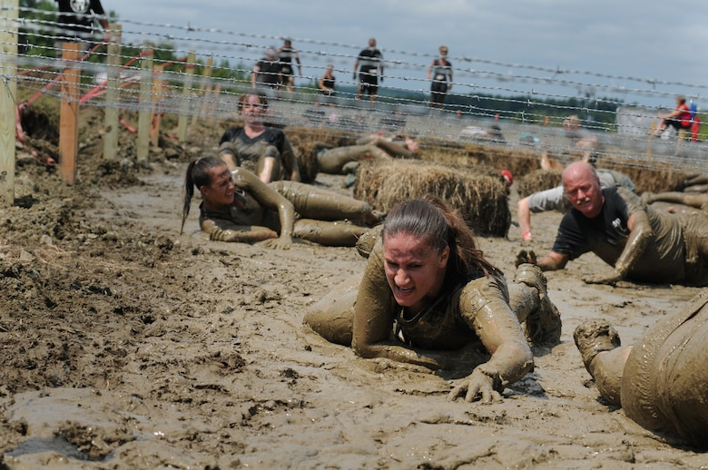 Staff Sgt. Ashley Davin, 102nd Security Forces Squadron, low crawls through the mud in Amesbury, Mass., Aug. 11, 2012. Davin was participating in the Spartan Race, testing her strength, endurance, and resilience against a course of challenging obstacles. (Air National Guard photo by Senior Airman Jeremy Bowcock/Released)