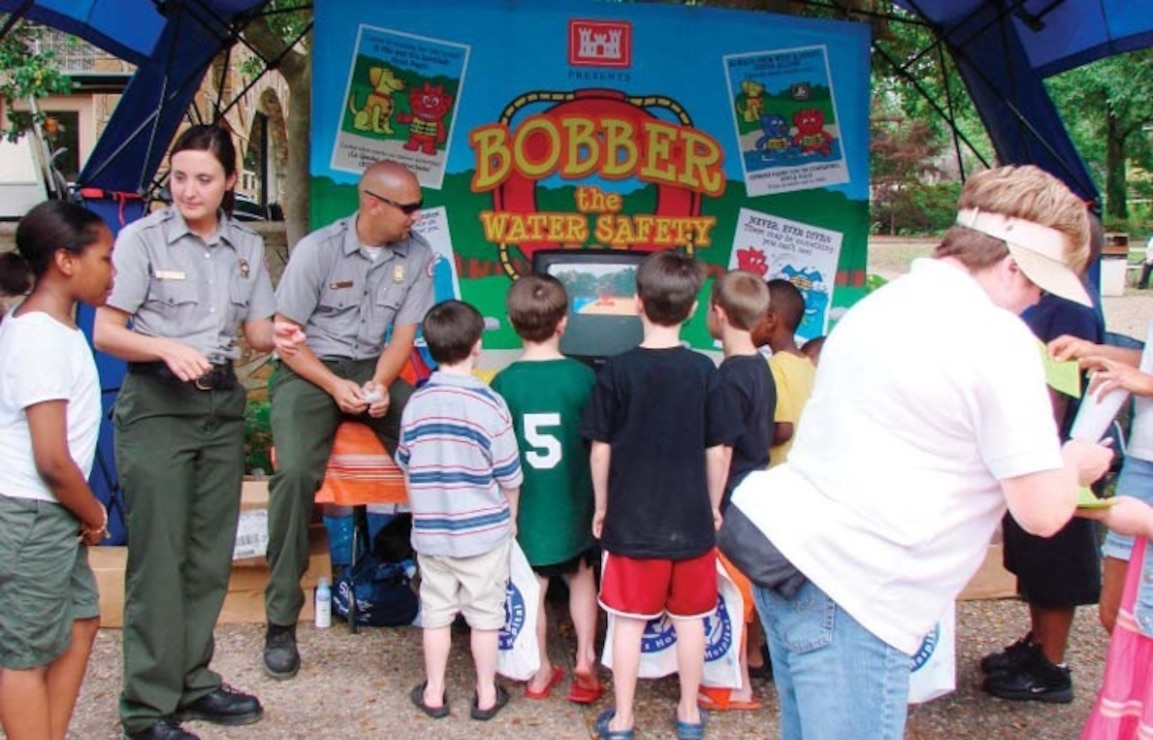 "US Army Corps of Engineers Park Rangers man a ""Bobber the Water Safety Dog"" display"