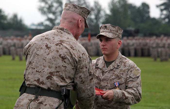 Philadelphia native Cpl. Jason M. Hassinger (center right), receives the Silver Star from Maj. Gen. John A. Toolan, the outgoing commanding general of 2nd Marine Division during the 2nd Marine Division change-of-command ceremony Aug. 23 aboard Camp Lejeune. Hassinger received the Silver Star for his actions during an ambushed patrol in Marjah, Helmand province, Afghanistan, in which he led his section through intense fire to rescue a group of fellow Marines pinned down by the enemy.  Hassinger was shot four times during the incident but continued to fight until the enemy retreated.  The Silver Star is the third-highest award a U.S. service member can receive for valor in combat.