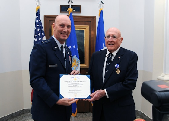 Maj. Gen. Timothy Zadalis (left), Air Education and Training Command director of Intelligence, Operations and Nuclear Integration, presents the Distinguished Flying Cross to former Army Air Corps 2nd Lt. Samuel  W.  Smith, 360th Bombardment Squadron B-17 aircraft commander, during a ceremony at Bldg. 100 at Joint Base San Antonio-Randolph Aug. 24. During WWII, Lieutenant Smith's display of exemplary knowledge and outstanding Airmanship under extreme and hazardous conditions culminated in the successful landing of his damaged aircraft upon a return from a mission to Hopston, Germany. (U.S. Air Force photo by Rich McFadden)