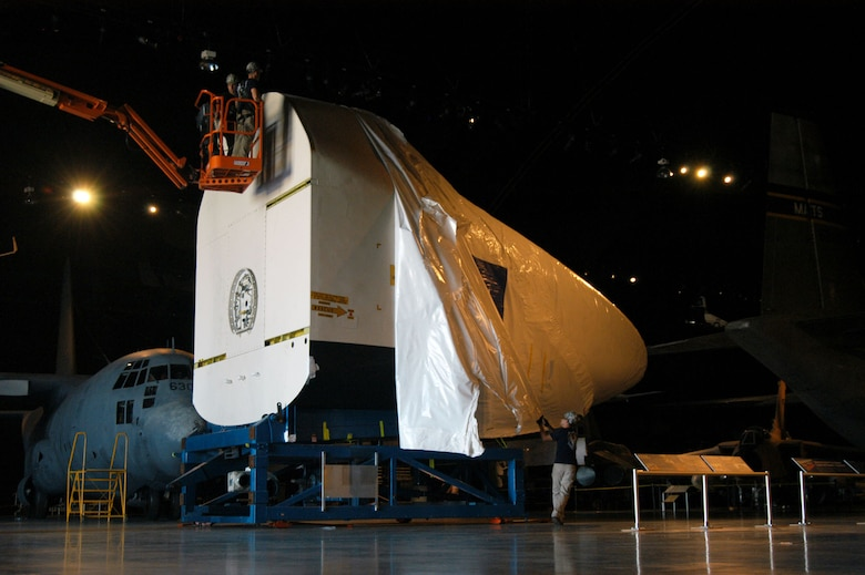 DAYTON, Ohio -- Restoration specialists from the National Museum of the U.S. Air Force remove the shrink-wrap from NASA's first Crew Compartment Trainer (CCT-1) in the museum's Cold War Gallery on Aug. 23, 2012. (Photo courtesy of Ron Kaplan)