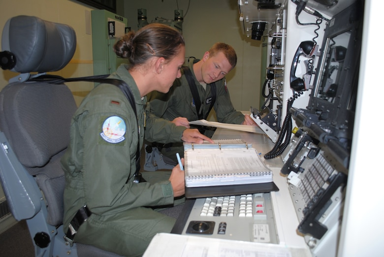 2nd Lt. Stephanie Guenther, 490th Missile Squadron deputy combat crew commander, and Capt. Brian Marlow, 490th MS ICBM combat crew commander, use their checklists while practicing possible scenarios in the missile procedures trainer. The pair of missileers will be representing the 490th MS in the upcoming Global Strike Challenge Sept. 9 to 13.  (U.S. Air Force photo/Airman 1st Class Katrina Heikkinen)