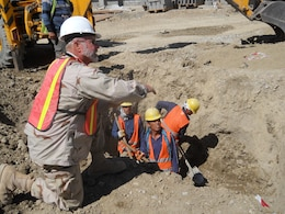 John Lindsay discussing safety procedures with workers in Afghanistan.