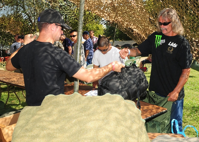 A volunteer from Beale Air Force Base, Calif., provides a new sleeping bag for Cole Young, a homeless U.S. Army veteran during the 2012 Veteran's Stand Down at River Bottoms Park in Marysville, Calif., August 24, 2012. The annual stand down provided basic needs, such as medical, financial, mental and religious services to veterans and their families and especially targeted homeless and less fortunate veterans. (U.S. Air Force photo by Senior Airman Shawn Nickel)