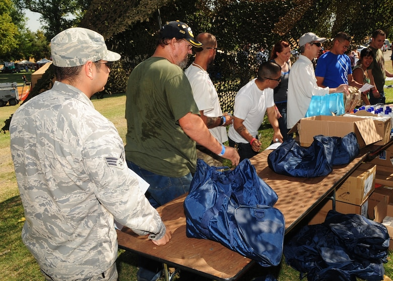 Veterans line up to receive clothing, sleeping bags and backpacks during the 2012 Veteran's Stand Down at River Bottoms Park in Marysville, Calif., August 24, 2012. Each veteran was escorted by a Beale Air Force Base, Calif., Airman. (U.S. Air Force photo by Senior Airman Shawn Nickel)