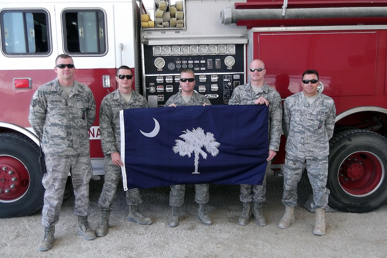 Tech. Sgt. Justin McKeown, Staff Sgt. Daniel Tatum, Staff Sgt. Scott Westmoreland, Tech. Sgt. Derek Hunter, and Master Sgt. Matthew Williams, fire fighters from the 169th Civil Engineering Squadron at McEntire Joint National Guard Base, S.C., pose for a photo in front of a fire truck while deployed to Bahrain, 2012.