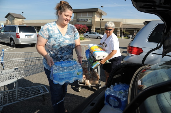 Darlene Gnuschke, Air Force retired and Biloxi resident, receives help from Maria Ainaga, head bagger at the base commissary with loading cases of water and other hurricane supplies into her trunk Aug. 27, 2012, at Keesler Air Force Base, Miss.  Keesler personnel are taking preventative measures to prepare and protect themselves and Keesler's assets as the base commander has declared HURCON 3, meaning destructive winds of 58 MPH or greater are expected as Hurricane Isaac approaches. (U.S. Air Force photo by Kemberly Groue)