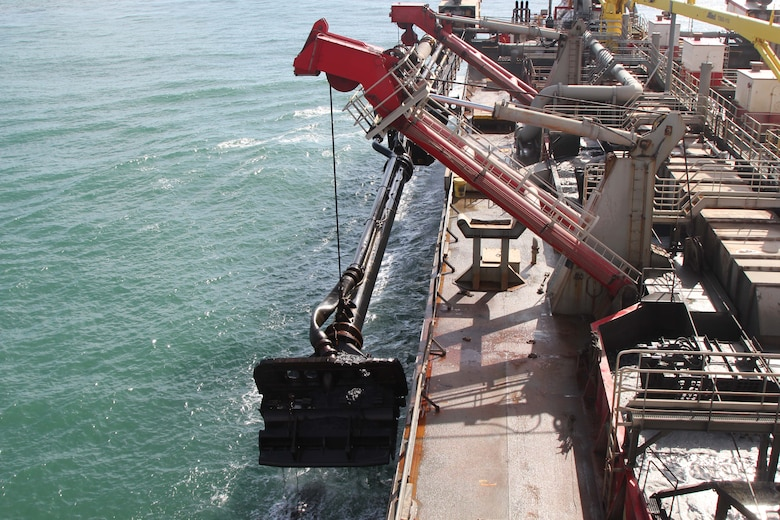 The arm of the hopper dredge is lowered to the harbor floor where it sucks material onto the vessel.