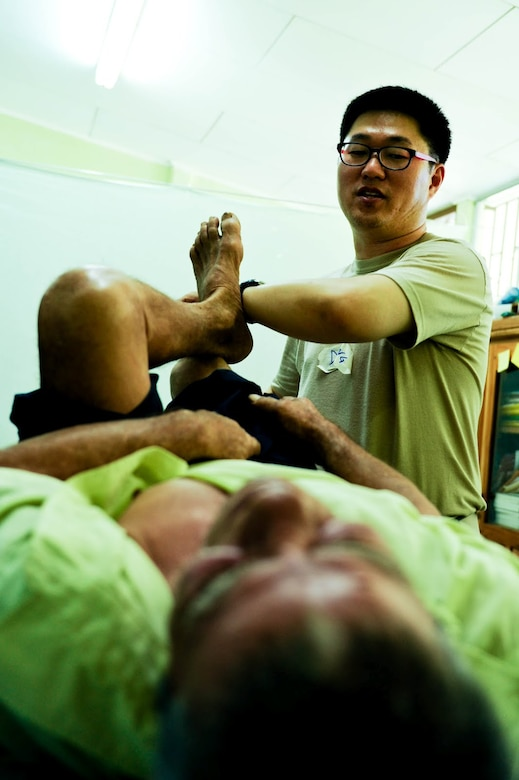 Air Force Maj. John Song, Medical Element Flight Surgeon, shows a Costa Rican patient stretches to alleviate back pain during a two-day joint Medical Readiness Training Exercise. Together with Costa Rica's Ministry of Health and Social Services, JTF-Bravo delivered medical care to 704 patients.