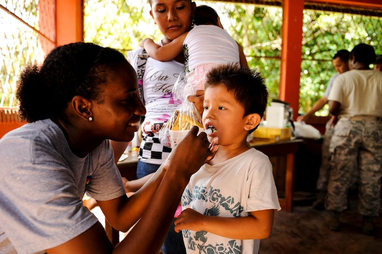 Air Force Tech. Sgt. Q-Anna Taylor, Medical Element NCO in charge of Environmental Health, gives a Costa Rican child de-worming medicine during a two-day joint Medical Readiness Training Exercise. Together with Costa Rica's Ministry of Health and Social Services, JTF-Bravo delivered medical care to 704 patients. (U.S. Air Force photo/1st Lt. Christopher Diaz)