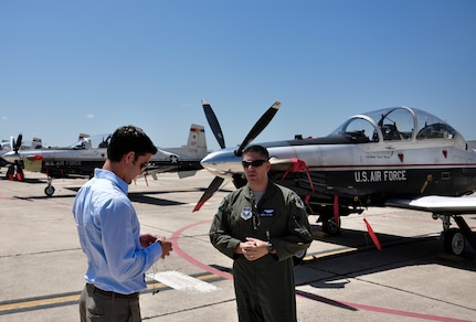 Lt. Col. Marc Stitzel, 455th Flying Training Squadron director of operations, talks with Phil Anaya, KENS5 anchor and reporter, about the evacuation of aircraft from Naval Air Station Pensacola, Fla., to Joint Base San Antonio-Randolph,Texas, in preparation for Tropical Storm Isaac's landfall. (U.S. Air Force photo by 2nd Lt. Keenan Kunst)