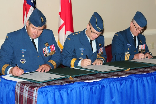 Lt. Col. Peter Dozois, left, Brig. Gen. Christopher Coates and Lt. Col. Patrick Carpentier sign documents signifying a change of command for the Canadian Detachment at Tinker Air Force Base on Aug. 15 at the Tinker Club. Colonel Carpentier relinquished command of the detachment to Colonel Dozois, while General Coates served as the presiding officer. (Air Force photo by Kelly White)