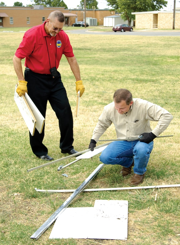 Hazards can often be eliminated without waiting for official safety workers to take care of it. Voluntary Protection Program members encourage Tinker personnel to remedy any hazard if they can do it without injuring themselves. A pile of broken furniture in the soccer field near base housing is easy to remedy as Doug Bynum, 72nd Civil Engineering contracting officer representative, left, and Darren Hulsey, 72nd Air Base Wing VPP Integrated Design Team member, show by loading the debris into the back of a pickup and taking to a proper base dumpster. Even after a self-help fix, VPP members say a quick report is still necessary, but easy to do by calling or doing it online at the Tinker home page. (Air Force photo by Margo Wright)