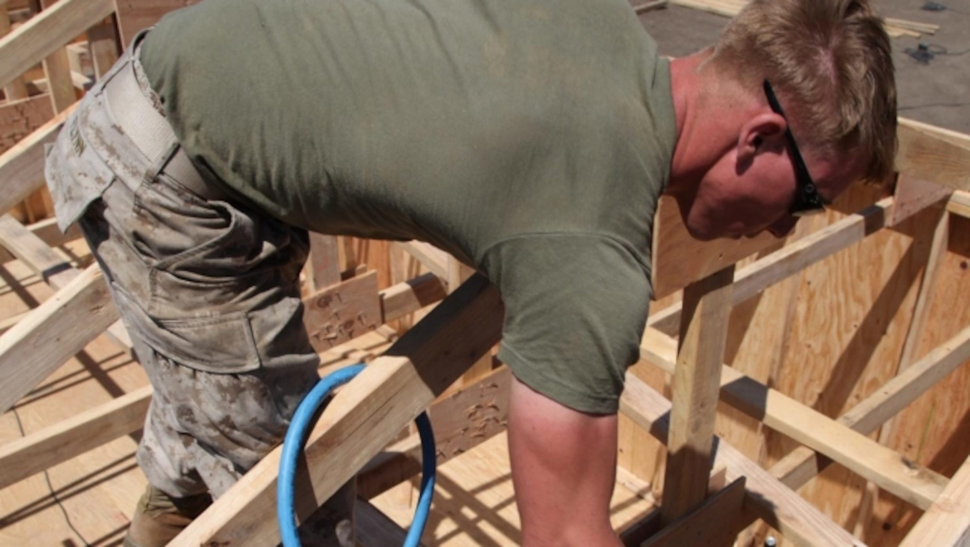 Cpl. Matthew R. Flynn, an assistant squad leader with Engineer Detachment, Combat Logistics Battalion 11, 11th Marine Expeditionary Unit, uses a nail gun to secure part of the structure of a Southwest Asia hut during a field operation at Camp Pendleton, Calif., June 20. Constructing the hut readied them for any humanitarian assistance or disaster relief missions where infrastructure damage has occurred.