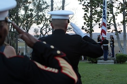 Service members render honors as Marines lower the nation ensign at the historical Santa Margarita Ranch House during Camp Pendleton's Evening Colors Ceremony, Aug. 28.