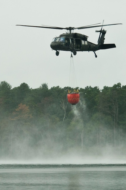 "A Massachusetts Army National Guard UH-60 Blackhawk helicopter, from the Army Aviation Support Facility #1 on the Massachusetts Military Reservation, hovers over Snake Pond in Sandwich, Mass., after it fills a ""Bambi Bucket"" with water during a demonstration of the firefighting system for Paraguayan air force pilots, Aug. 28, 2012. Five Paraguayan air force pilots were in Massachusetts as part of the National Guard State Partnership Program, a 20-year-old program that partners states with countries around the world to facilitate cooperation across all aspects of civilian-military affairs and encourage people-to-people ties at the state level. (Air National Guard photo by Master Sgt. Aaron Smith/Released)"