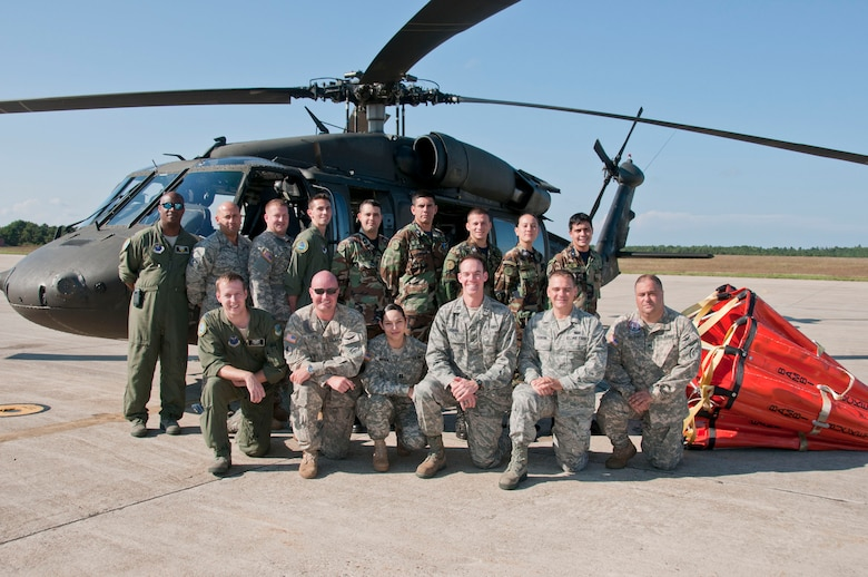 "Massachusetts National Guard members and Paraguayan air force pilots pose in front of a Massachusetts Army National Guard UH-60 Blackhawk helicopter and a ""Bambi Bucket"" after a demonstration of the firefighting system at The Massachusetts Military Reservation, Aug. 28, 2012. The Paraguayan air force pilots were in Massachusetts as part of the National Guard State Partnership Program, a 20-year-old program that partners states with countries around the world to facilitate cooperation across all aspects of civilian-military affairs and encourage people-to-people ties at the state level. (Air National Guard photo by Master Sgt. Aaron Smith/Released)"