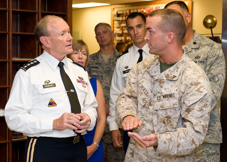 Army Gen. Martin E. Dempsey, 18th Chairman of the Joint Chiefs of Staff, listens as Marine Lance Cpl. Landon Beaty, Marine Corps Liaison, explains the process of preparing uniforms for fallen heroes Aug. 10, 2012, at the Charles C. Carson Center for Mortuary Affairs, Dover Air Force Base, Del. Dempsey and his wife Deanie met with Soldiers, Sailors, Airmen and Marines during their visit. (U.S. Air Force photo/Roland Balik)