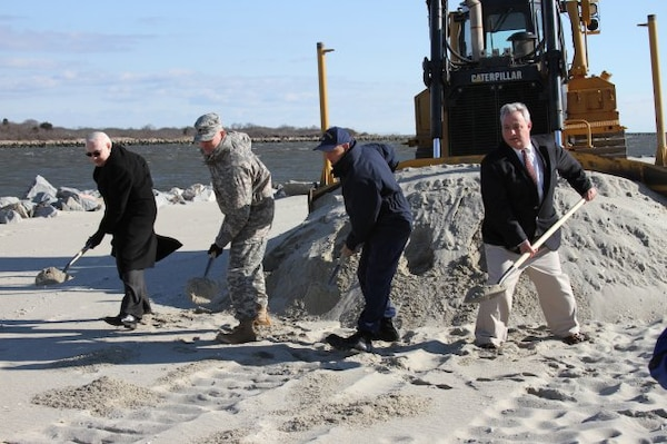 Cape May City Mayor Ed Maheney, U.S. Coast Guard Capt. William Kelly, USACE Philadelphia District Commander Lt. Col. Philip M. Secrist, and Ben Kaiser of the New Jersey Department of Environmental Protection shovel the last load of sand onto Cape May as part of a $9 million nourishment project.