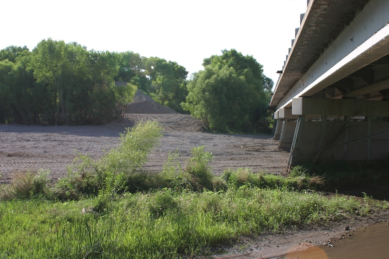 Emergency work by the NMDOT removed 3-5 feet of sediment and debris to increase channel capacity under the Highway 180 Bridge over the Gila River. The sediment is seen piled in the background.  The bridge is approximately 40 miles downstream from the Whitewater-Baldy Fire's burn area.